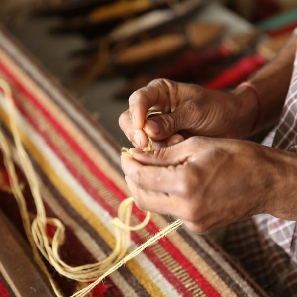 Close-up of a woman weaving a rug by hand.