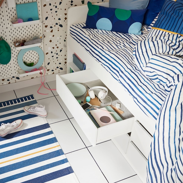Close-up of an IKEA SLÄKT bed, with blue striped bed linen, with one of four drawers pulled out to reveal books and headphones.
