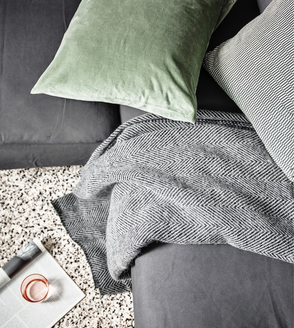 Close-up of an IKEA STRIMLÖNN throw with herringbone design on a gray sofa, with a green cushion.