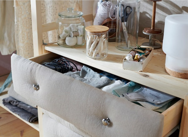 Close-up of an open chest of drawers, with fabric attached to the front.
