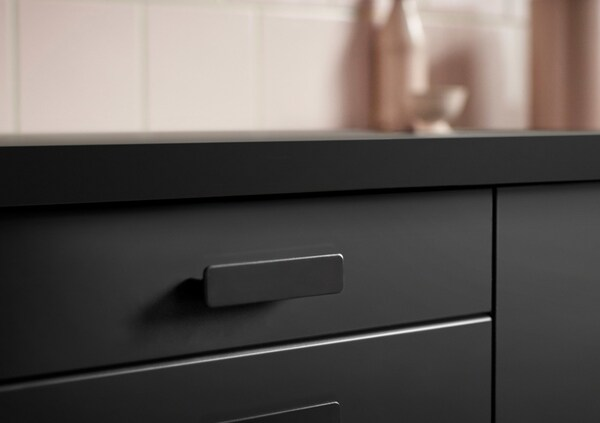 Close-up of black drawer front with a black hnadle.