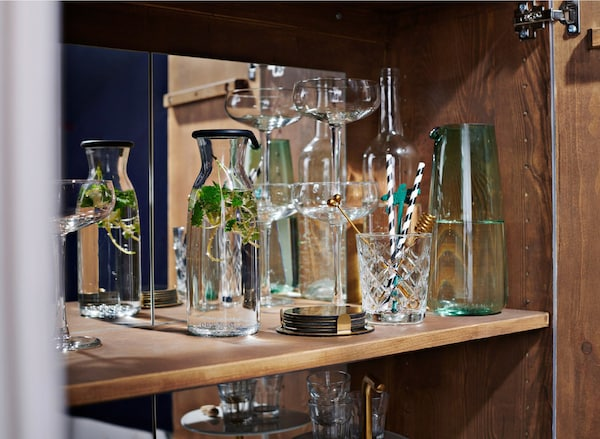 Close-up of drinking glasses and a carafe inside a cabinet.