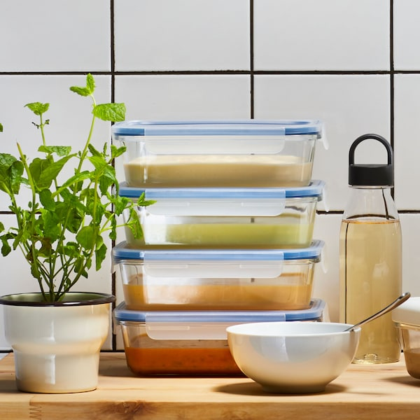 Close up of four stacked food containers filled with food and a clear water bottle with black lid.
