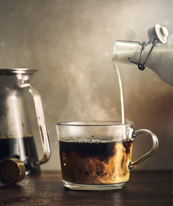 Close-up of milk being poured into coffee in a glass cup.