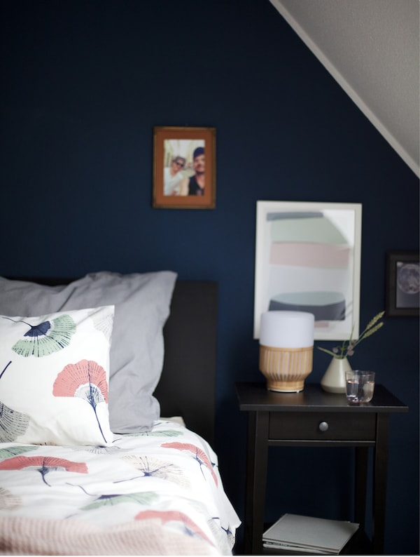 Close-up of one side of a bed with a lamp and pictures on the wall.