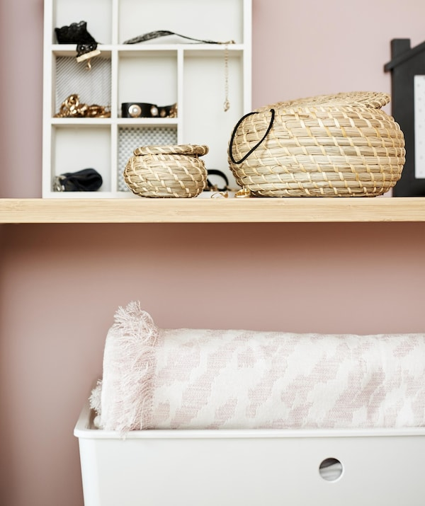 Close up of small baskets and storage boxes on shelves.