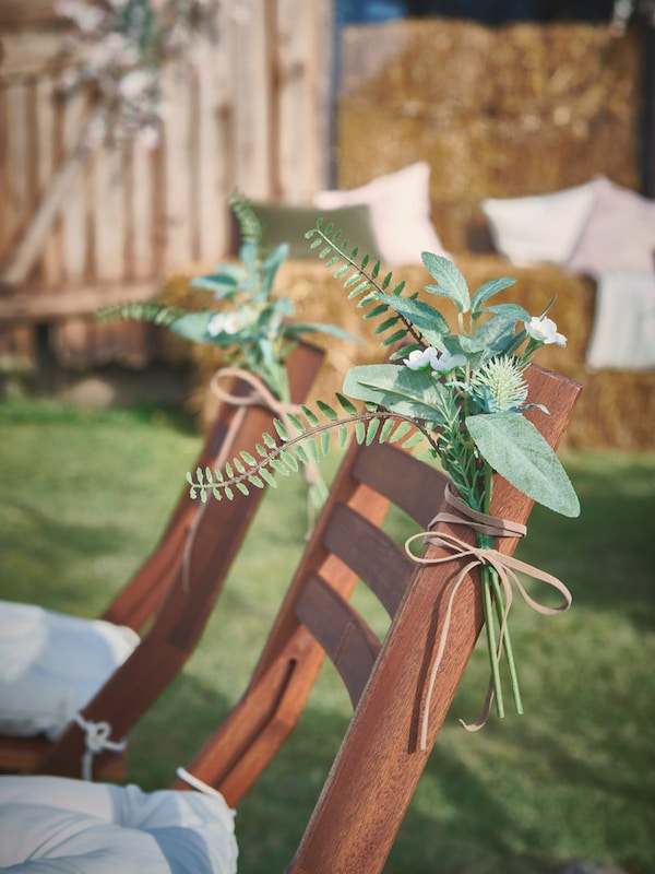 Close up of SMYCKA artifical bouquet tied to the back of a rustic wedding chair