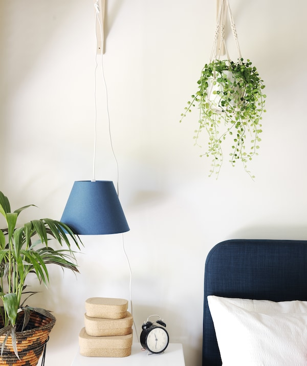 Close up of the corner of a bed and bedside table with small stacked boxes and plants.