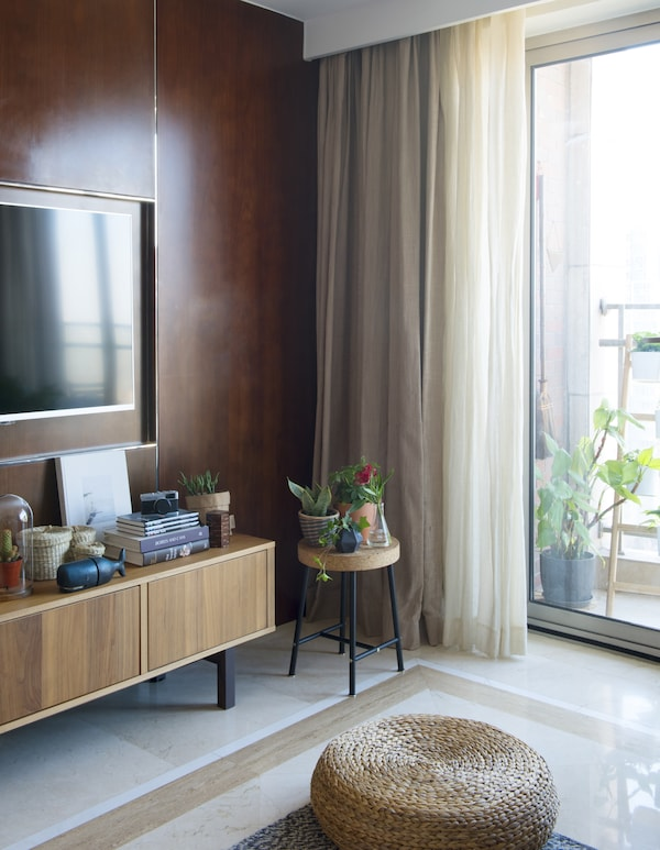 Close-up of the corner of a living room with brown sideboard and stool.