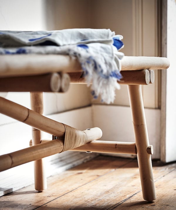 Close-up of the corner of a TÄNKVÄRD rattan bench, with folded fabric on top of the bench.