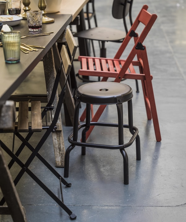 Close up of the edge of a dining table with mismatched chairs.