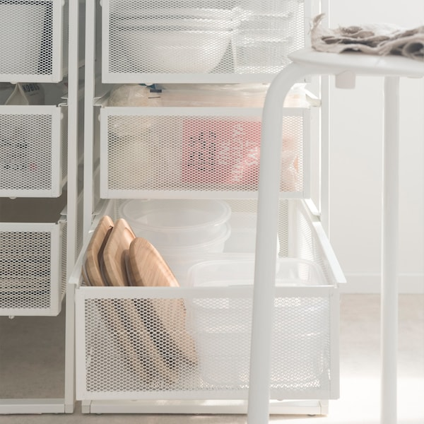 Close-up of two IKEA LENNART draw units behind a stool, filled with tableware and groceries.