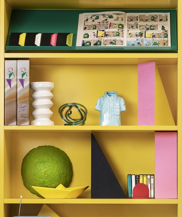 Close-up of two shelves of a bright yellow bookcase with ornaments on them.