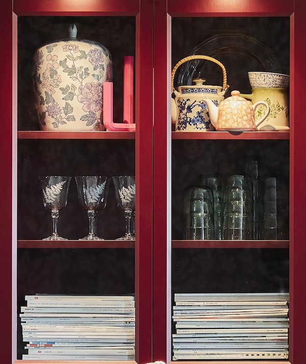 Close-up of two shelves of a red bookcase with ornaments on them.