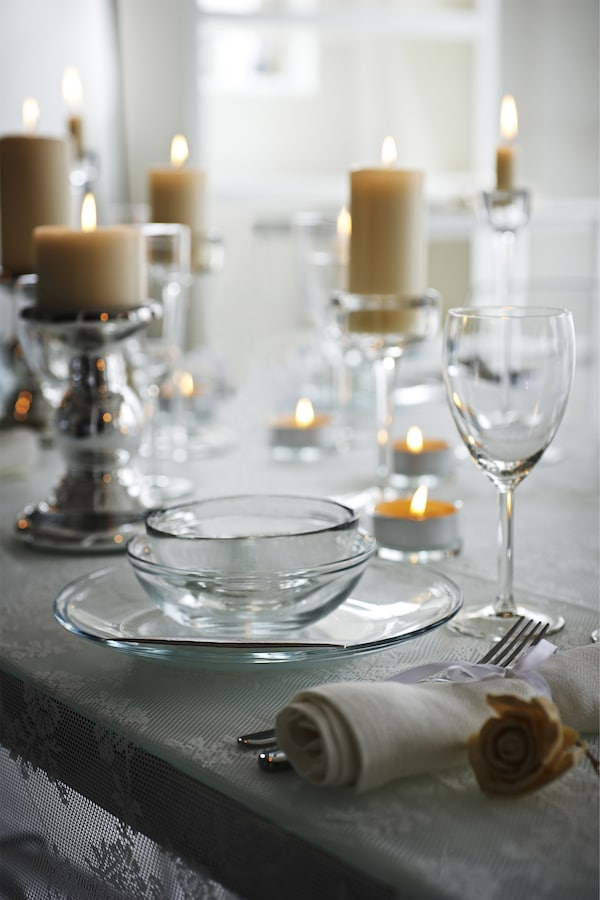 Close-up of warmly lit candles in glass candlesticks next to glass dinnerware.