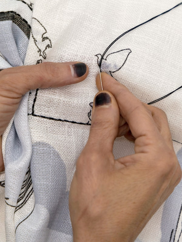 Close-up showing the hands of an artisan who embroiders a pigeon and other details on a printed cushion cover.