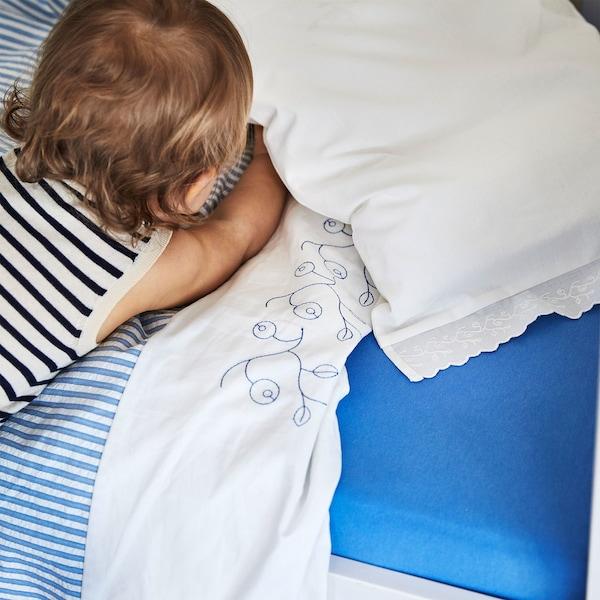 Close-up van een baby die ligt op een wit-blauw gestreept GULSPARV dekbedovertrek uit 100% katoen met bosbessenmotief.