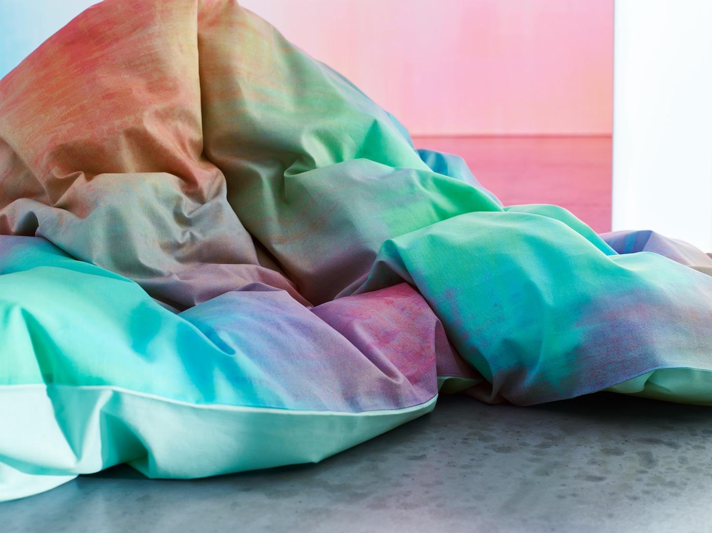 Close‑up van een PIPSTÄKRA dekbedovertrek met pastelprint die lijkt op een waterverfschilderij.