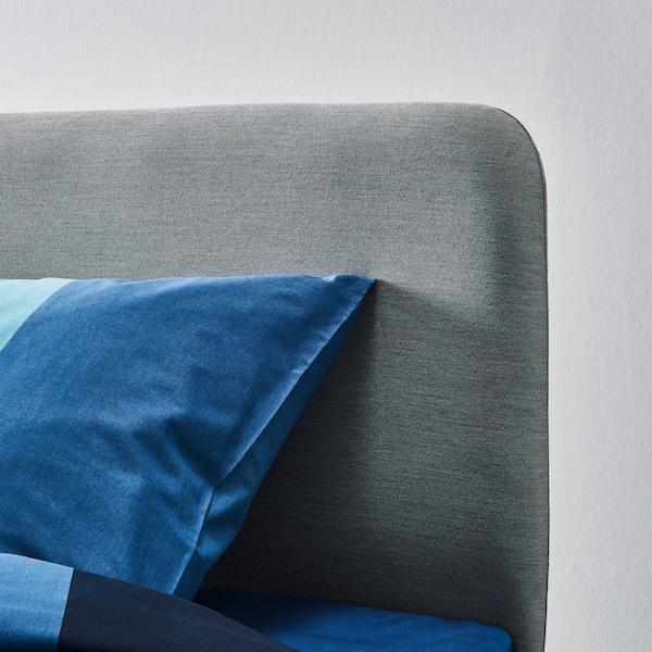 Close‑up van het hoofdeinde van het grijze beklede SLATTUM bed.
