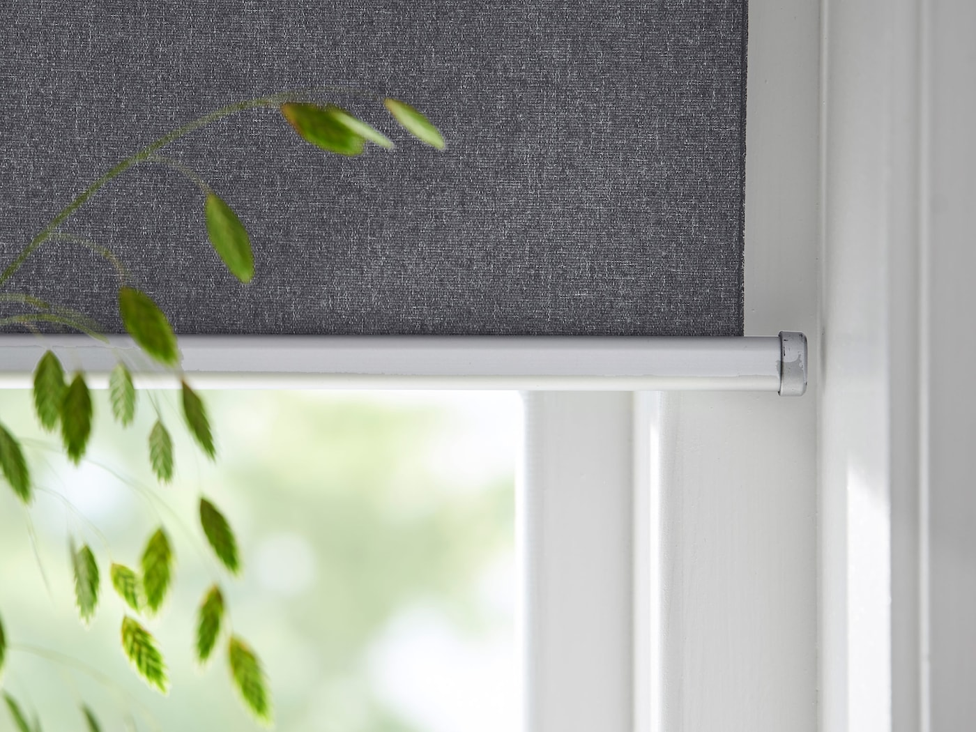Close-up view of a FYRTUR smart window blind with houseplant in foreground.