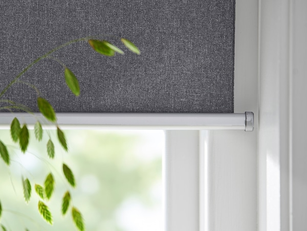 Close-up view of an IKEA smart window blind with houseplant in foreground.