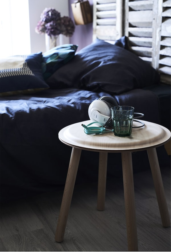 Closeup of a wooden stool being used as a bedside table to hold headphones and a glass of water.