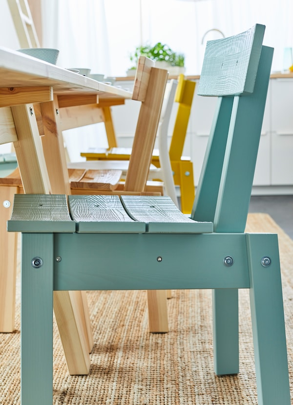 Closeup of an IKEA INDUSTRIELL blue seat by a dining table.