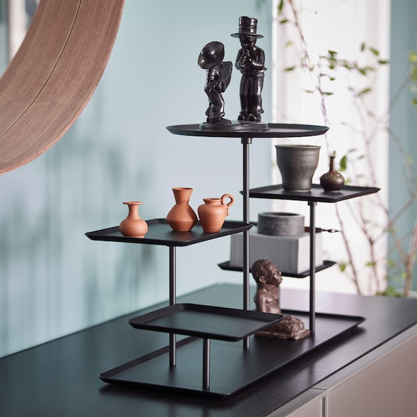 Closeup of black IKEA SAMMANHANG black display stand with square and round pedestal trays holding figurines and items.