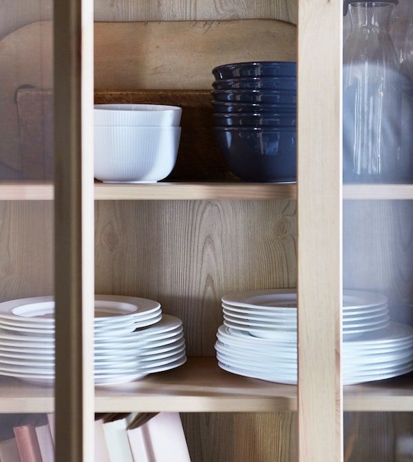 Closeup of dinnerware stacked in a wooden cabinet with glass doors.