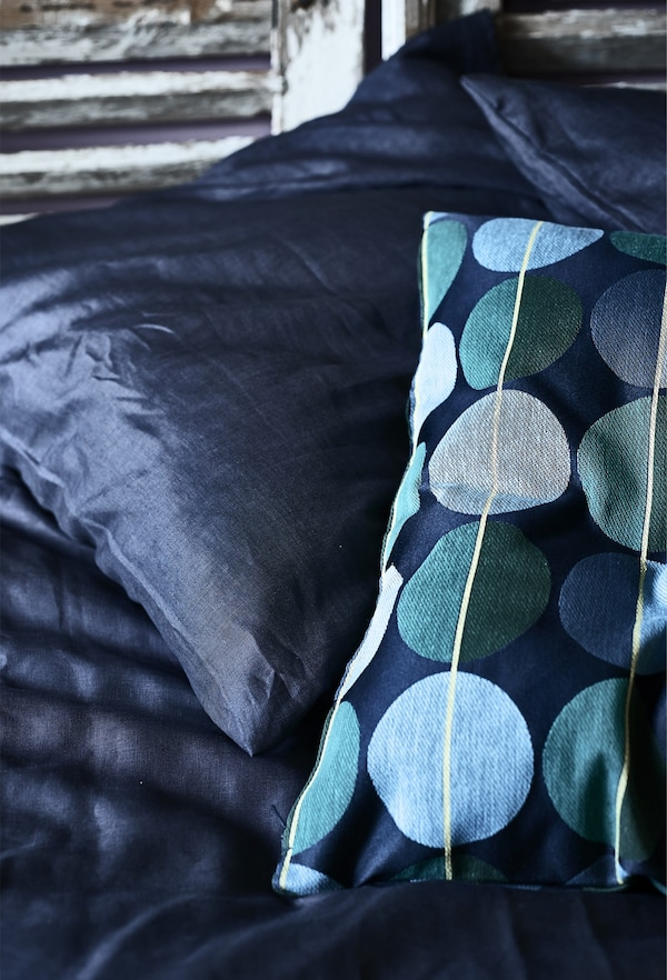 Closeup of IKEA dark blue and circle patterned cushions.