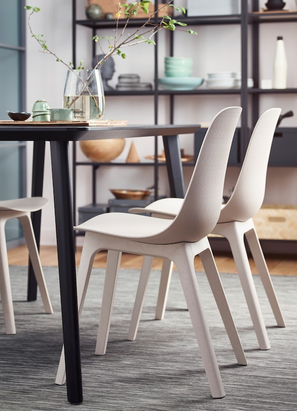 Closeup of two IKEA ODGER white recycled plastic chairs.