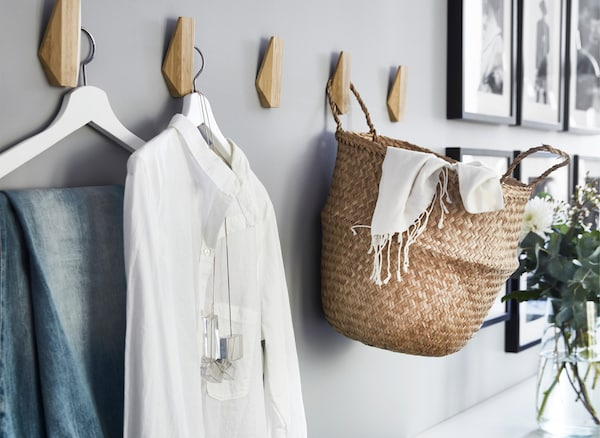 Clothes and a basket hanging on wooden hooks on a gray wall.