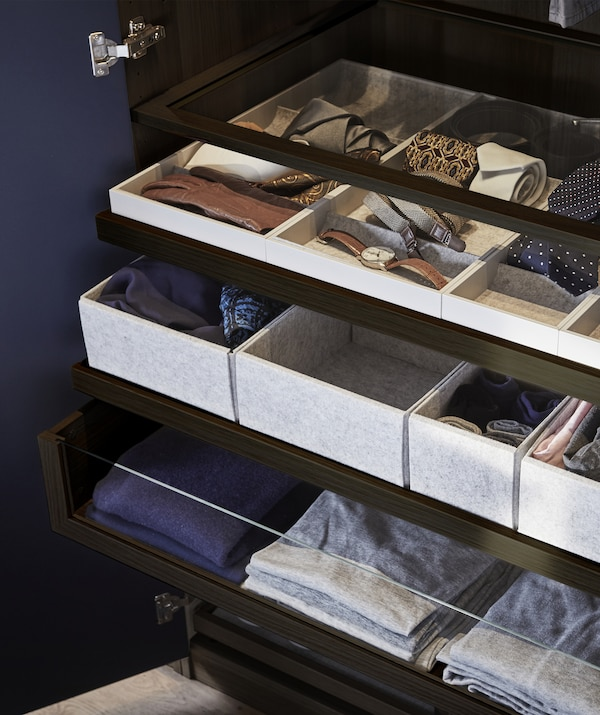 Clothes and accessories stored in drawers, trays, inserts and shelves.