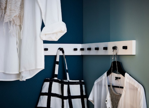 Clothes and bags hanging from knobs in the corner of a room.