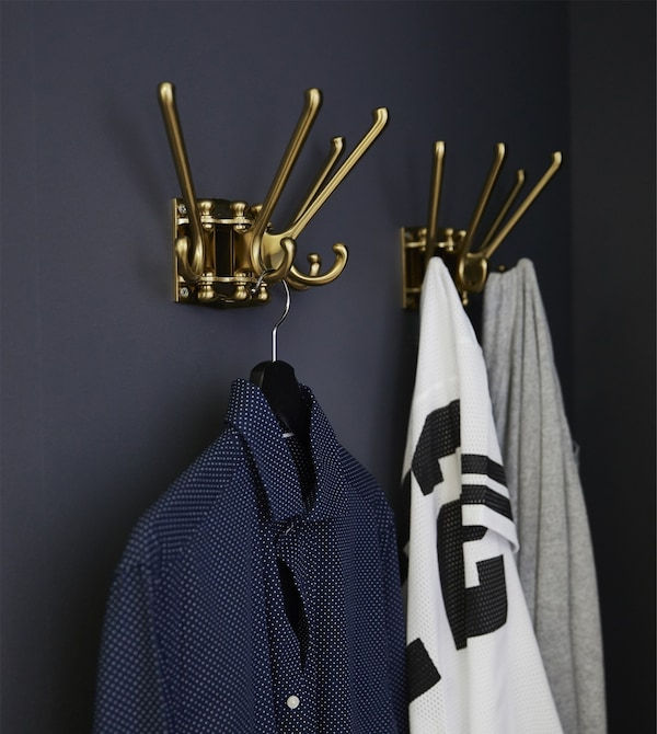 Clothes hang from two KÄMPIG 4-armed swivel hooks mounted on a dark grey wall.