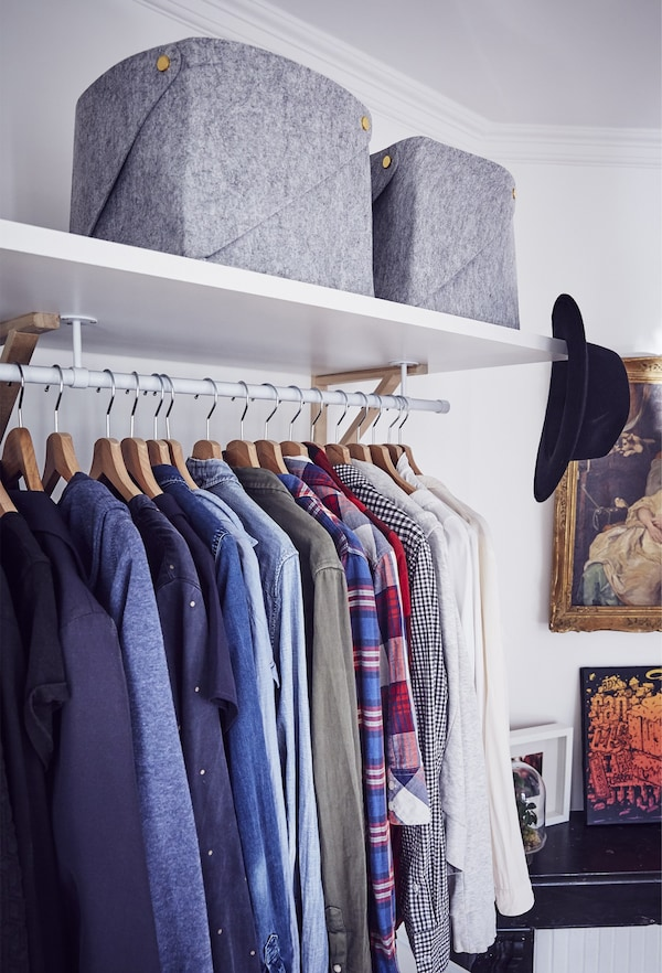 Clothes hang in an open-storage wardrobe.