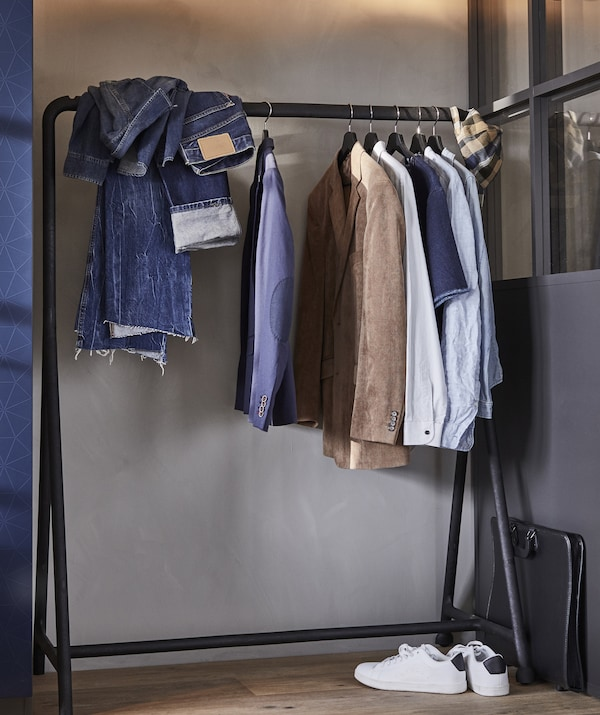 Clothes hanging on a black open clothes rail against a pale grey wall.