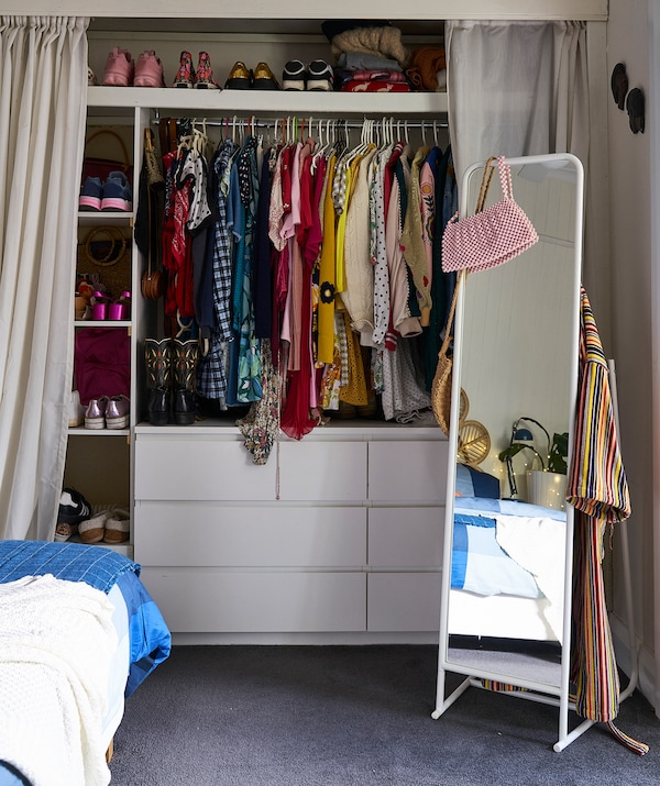 Clothes hanging on a rail and shoes on shelves above two chest of drawers, with curtains either side and a free-standing mirror.