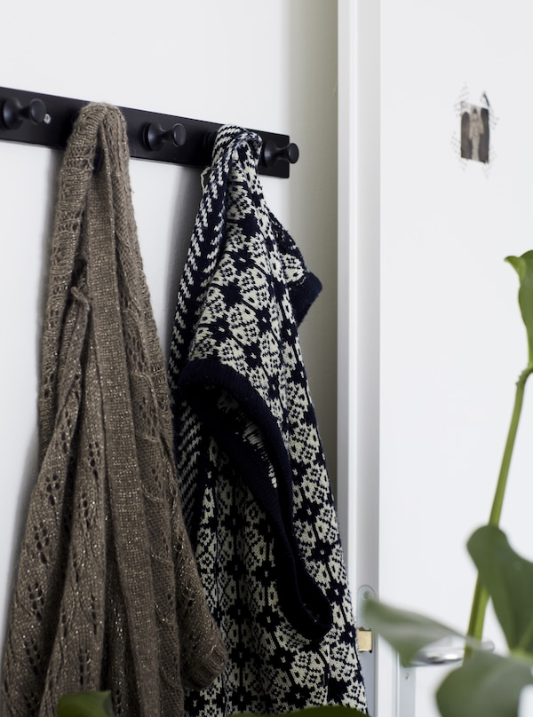 Clothes hanging on a row of hooks.