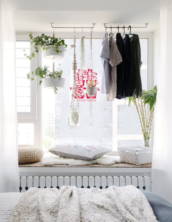 Clothes hanging on rails in a window alcove.