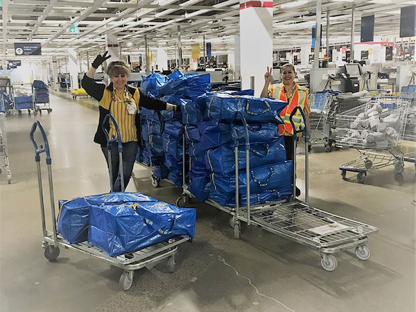 Co-workers from the IKEA Montreal Store stand by carts with IKEA bags filled with products.