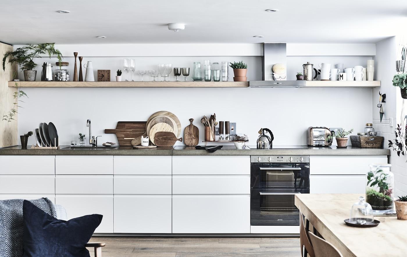 Cocina blanca en línea con encimeras y estantes de hormigón y estantes de almacenaje abierto.