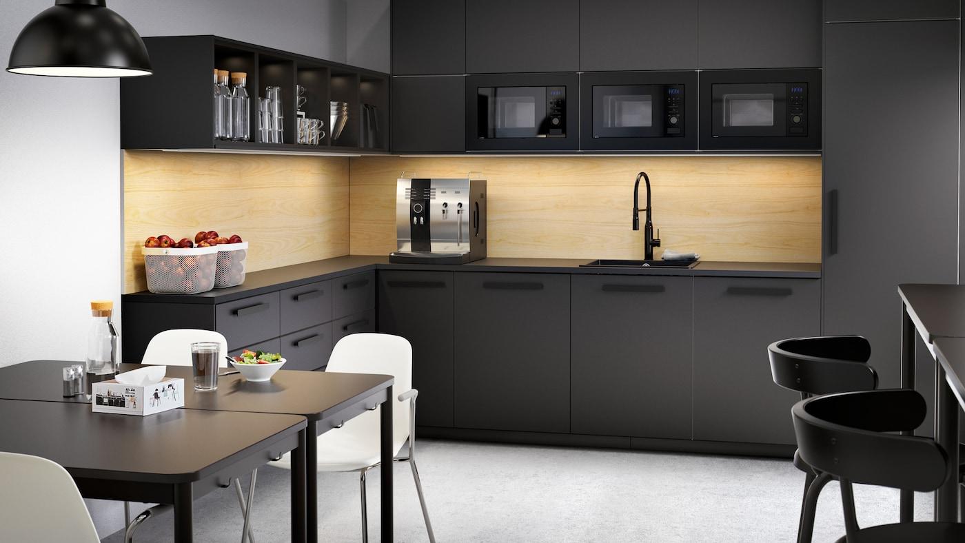 Cocina negra grande con cajones y armarios, una cafetera, cuencos de fruta y dos mesas con sillas blancas.
