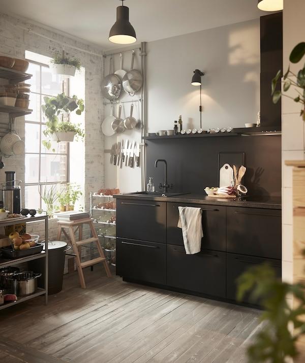 Cocina negra IKEA METOD con utensilios colgados en la pared