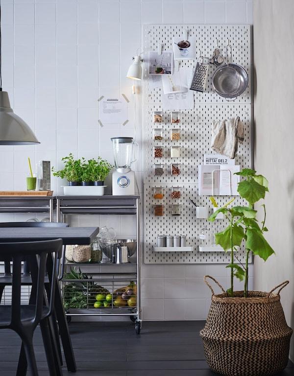 Cocina organizada con un panel perforado y un carrito