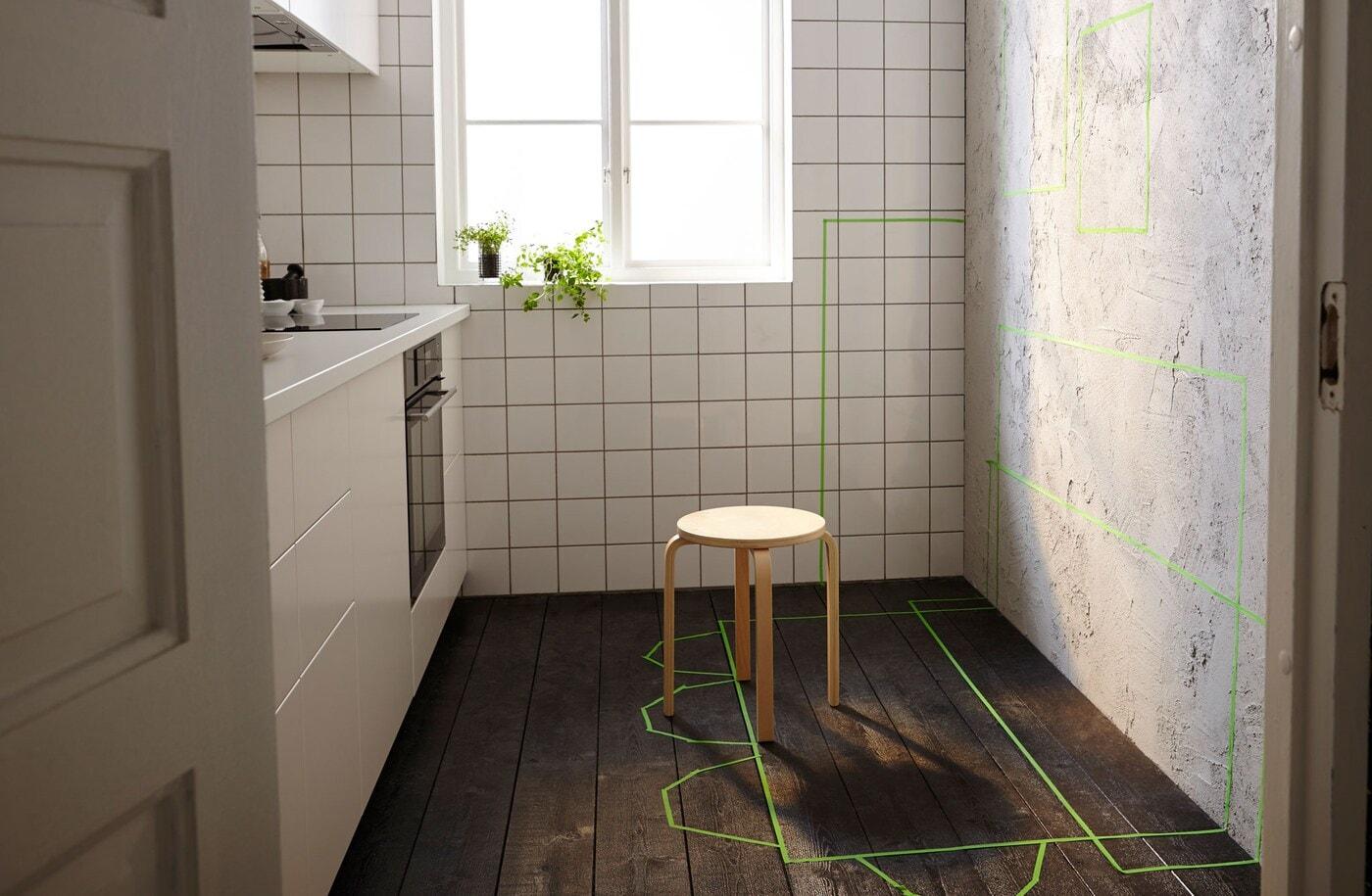 Cocina pequeña con una pared libre y una cinta verde que marca la posición de los futuros muebles de almacenaje, mesas y sillas.