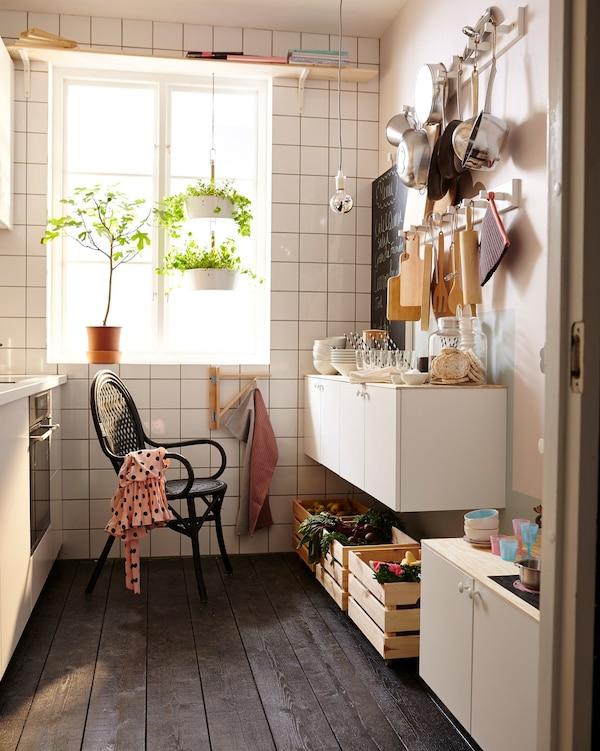 Cocina pequeña con una silla negra y una pared con utensilios de cocina.