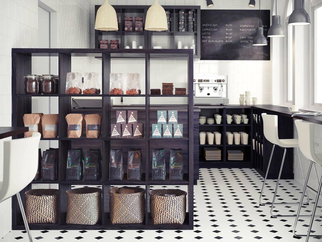 Coffeeshop mit dunklen KALLAX Regalen, KALLAX Raumteiler & verchromten BERNHARD Barhocker in weiß