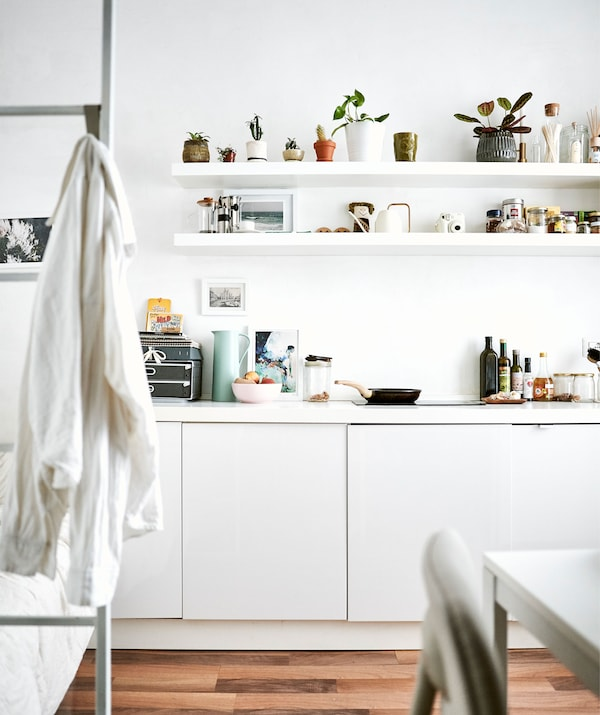 Coin cuisine en blanc avec étagères et échelle menant à la chambre en mezzanine.