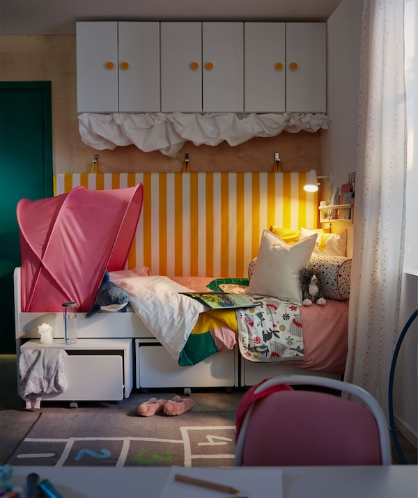 Coin dodo dans une chambre d'enfant. Un matelas est accroché au mur derrière le lit, on trouve aussi du rangement sous le lit et au mur.